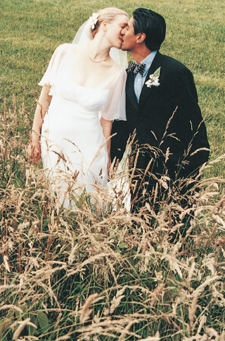 bride-and-groom-kiss-in-field-with-tall-grass