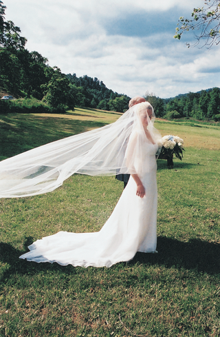 bride-in-countryside-with-bridal-veil-in-wind