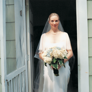 bride-holds-bouquet-with-white-and-blue-flowers