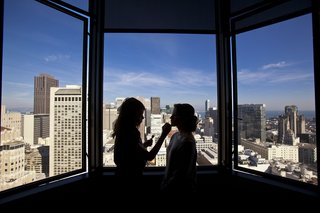 bride-getting-makeup-on-with-city-skyline-silhouette
