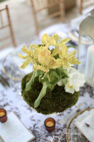 white-vase-with-moss-and-yellow-flowers-at-wedding