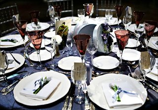 wedding-reception-table-with-blue-tablecloth-white-tableware-and-red-glassware