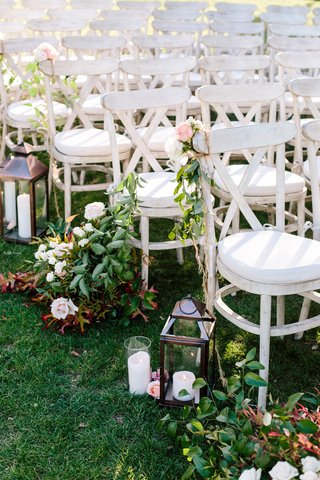 white-washed-ceremony-chairs-adding-a-rustic-look-lantern-aisle-decoration-greenery