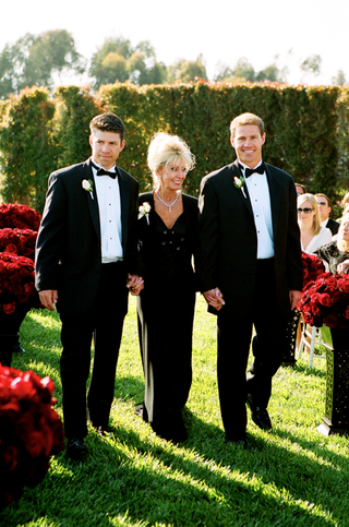 tuxedo-ushers-walk-mother-of-bride-down-grass-aisle