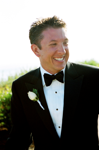 groomsman-wearing-tuxedo-with-bow-tie-and-rose