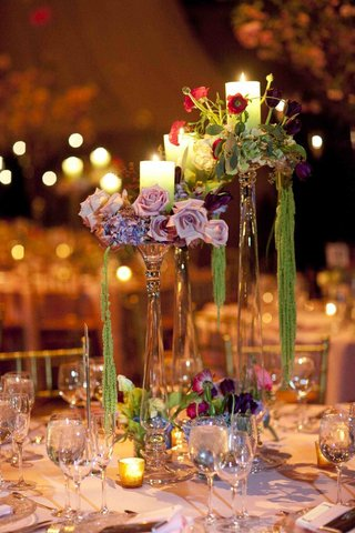 wedding-reception-centerpieces-of-crystal-candle-holders-with-candle-purple-green-and-red-flowers