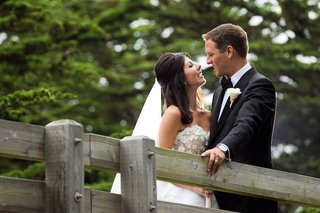 bride-and-groom-look-into-each-others-eyes-on-bridge