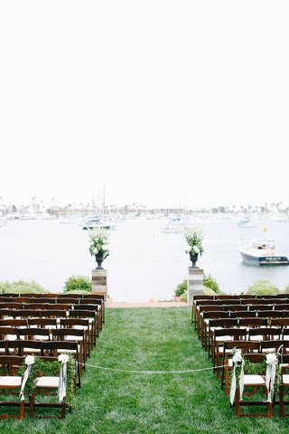 wood-ceremony-chairs-with-green-garlands-on-lawn-in-front-of-san-diego-bay