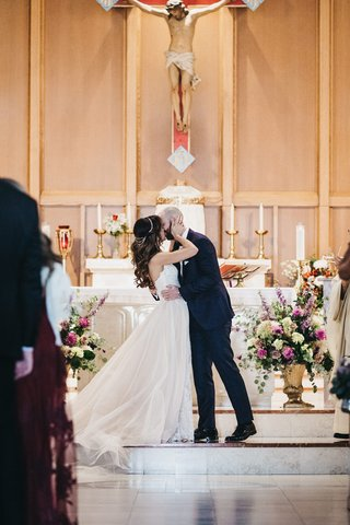 groom-kisses-bride-during-roman-catholic-church-ceremony