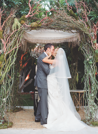 bride-in-a-carolina-herrera-gown-and-veil-kisses-groom-in-grey-suit-under-a-chuppah