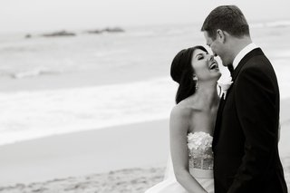 black-and-white-photo-of-couple-laughing-on-beach
