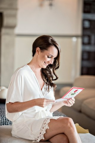 bride-viewing-card-from-groom-before-wedding-red-card-pre-ceremony-smiling-silk-robe-getting-ready