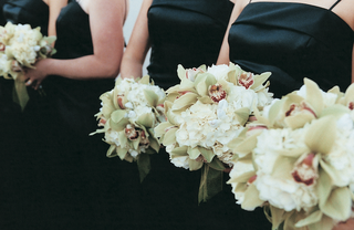 bridesmaids-wearing-black-gowns-hold-white-flowers