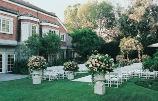 white-chairs-and-urns-of-flowers-set-up-in-backyard