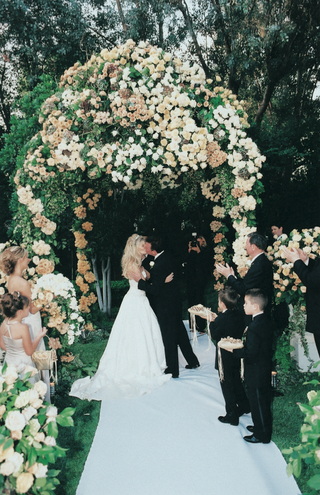 couple-kisses-under-gazebo-decorated-with-cream-flowers