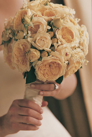 bride-holds-bouquet-of-white-roses