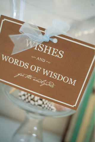 gold-and-white-sign-with-light-blue-ribbon-for-wishes-and-wisdom
