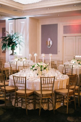 wedding-reception-round-table-with-gold-chairs-low-flower-centerpiece-and-tall-taper-candles-shades
