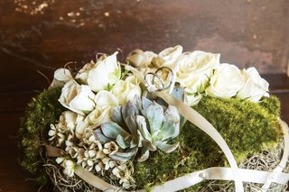two-wedding-rings-on-bed-of-moss-white-roses-succulents