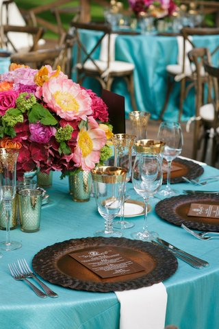 wedding-reception-table-with-dark-brown-plate-and-menu-with-wood-background