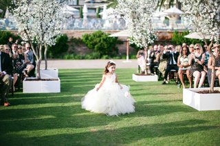 flower-girl-walking-down-grass-aisle-with-wand