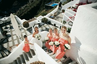 coral-bridesmaid-gowns-on-stairs-of-santorini