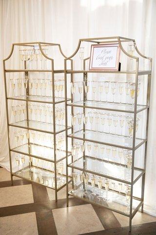 wedding reception champagne flutes for escort cards on gold bookcase etagere bookshelf