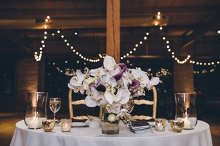 wedding-reception-rustic-design-white-and-purple-orchid-flower-arrangement-wood-beams-twinkle-lights