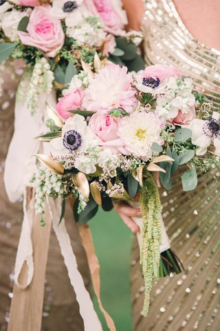 bridesmaid-in-sequin-gold-dress-holding-bouquet-of-anemone-dahlia-gold-leaves-amaranthus-pink