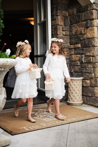 two-flower-girls-in-white-dresses-cardigans-and-flower-crowns