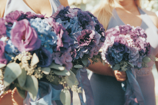 bridesmaids-holding-purple-and-blue-flowers