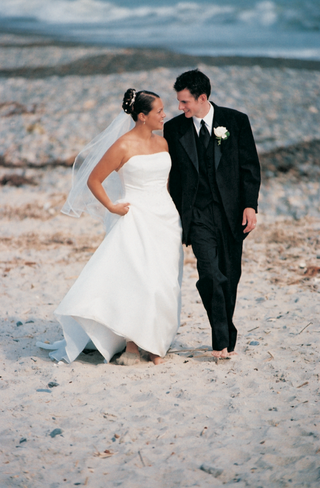 bride-and-groom-walk-on-the-beach-in-their-wedding-dress-and-tuxedo