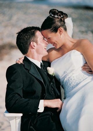 bride-and-groom-touch-foreheads-on-sand