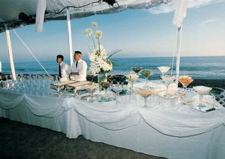 white-buffet-table-in-front-of-ocean-with-food-and-drink-spread