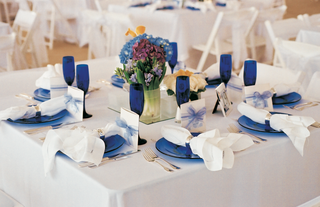 square-white-table-with-blue-plates-goblets-and-centerpieces