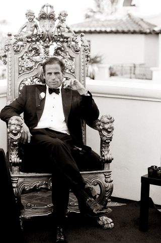 black-and-white-photo-of-groom-sitting-on-kings-throne