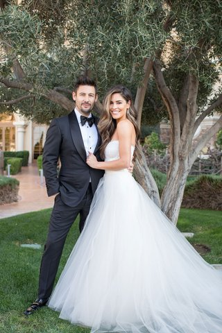 bride in strapless monique lhuillier wedding dress tulle skirt groom in tuxedo outdoor portrait