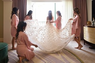 bride-in-galia-lahav-wedding-dress-embellished-skirt-in-sun-help-from-bridesmaids-in-pink-robes