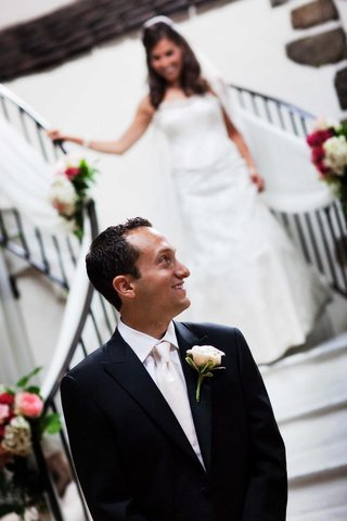 groom-in-white-tie-waits-for-his-bride-to-come-down-the-staircase