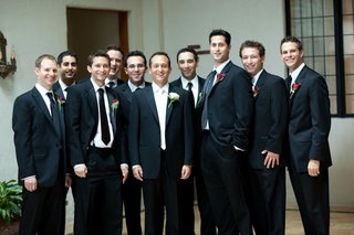 groom-with-ten-groomsmen-in-tuxedos-and-red-boutonnieres