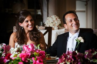 bride-and-groom-smile-at-sweetheart-table