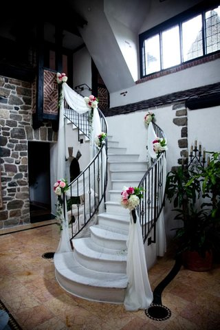 chateau-staircase-with-white-drapes-and-flower-arrangements