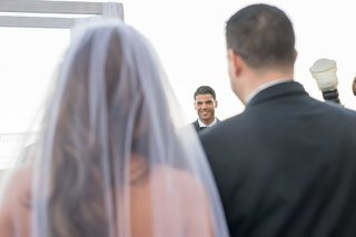 bride-in-veil-long-brunette-hair-groom-at-altar-looking-at-bride-for-first-time