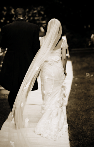 sepia-photo-of-bride-in-a-claire-pettibone-lace-gown-and-groom-in-black-tails-exit-the-ceremony