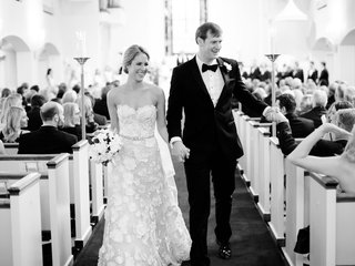 black and white photo of bride and groom newlyweds recessing aisle shaking hands of guests