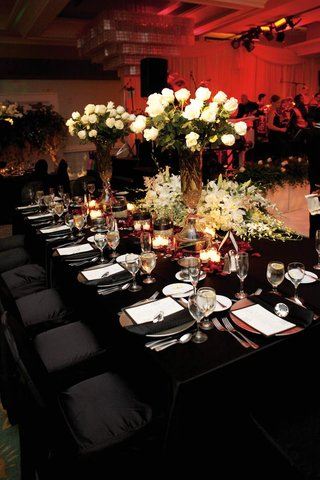 black-tablecloths-and-white-floral-arrangements