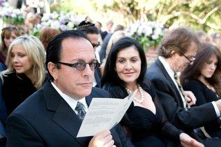 man-reading-wedding-program-in-earrings