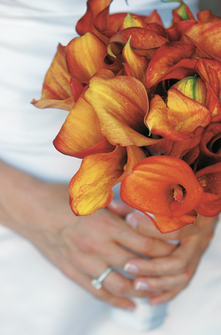 bride-holds-bouquet-of-orange-calla-lily-flowers