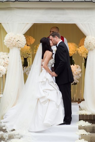 bride-and-groom-kiss-on-steps-at-white-gazebo