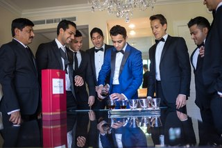 groom-in-blue-suit-groomsmen-in-black-suits-groom-pours-drinks